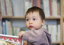 Niño en una biblioteca foto de archivo