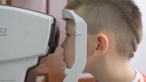 Niño en una clínica oftálmica Niño pequeño que mira un tonometer en el examen de la vista almacen de metraje de vídeo