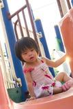 Niño en una diapositiva en patio Imagen de archivo