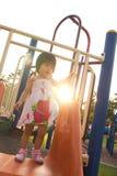 Niño en una diapositiva en patio Fotografía de archivo libre de regalías