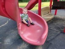 Niño en una diapositiva rizada roja imagen de archivo