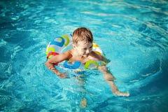 Niño en una piscina que tiene sus primeras lecciones de la nadada foto de archivo
