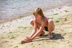 Niño en una playa que es arena jugada Imagen de archivo libre de regalías