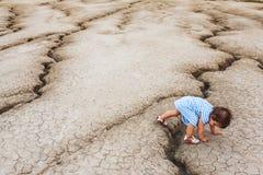 Niño en una tierra del desierto Imagenes de archivo