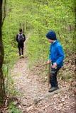 Niño en una trayectoria de bosque en primavera fotografía de archivo