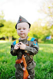 Niño en uniforme militar contra fondo de la naturaleza Imagenes de archivo