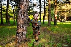 Niño en uniforme militar contra fondo de la naturaleza Fotografía de archivo