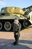 Niño en uniforme militar en el fondo del tanque Fotos de archivo