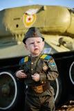 Niño en uniforme militar en el fondo del tanque Foto de archivo