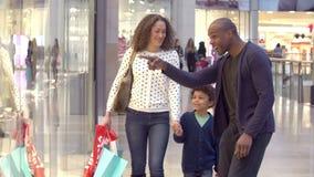Niño en viaje a la alameda de compras con los padres almacen de metraje de vídeo