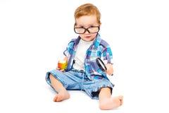 Niño en vidrios con una lupa Fotos de archivo