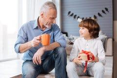 Niño encantado agradable que mira a su abuelo Foto de archivo libre de regalías