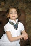 Niño encantador de la muchacha en una blusa blanca con un collar hermoso Imagen de archivo