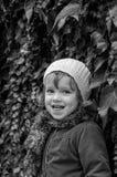 Niño encantador de la niña en un sombrero y una capa que se oponen a la pared con el día soleado del otoño de las uvas salvajes q Fotos de archivo