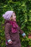 Niño encantador de la niña en un sombrero y una capa que se oponen a la pared con el día soleado del otoño de las uvas salvajes q Imágenes de archivo libres de regalías