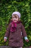 Niño encantador de la niña en un sombrero y una capa que se oponen a la pared con el día soleado del otoño de las uvas salvajes q Foto de archivo