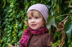 Niño encantador de la niña en un sombrero y una capa que se oponen a la pared con el día soleado del otoño de las uvas salvajes q Fotografía de archivo