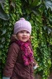 Niño encantador de la niña en un sombrero y una capa que se oponen a la pared con el día soleado del otoño de las uvas salvajes q Foto de archivo libre de regalías
