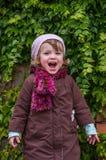 Niño encantador de la niña en un sombrero y una capa que se oponen a la pared con el día soleado del otoño de las uvas salvajes q Imagen de archivo libre de regalías