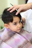 Niño encantador en el peluquero Foto de archivo