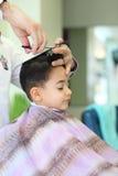 Niño encantador en el peluquero Fotografía de archivo