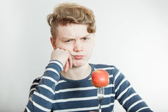 Niño enfadado con la bifurcación pegada en manzana Imágenes de archivo libres de regalías