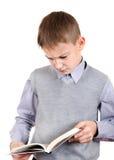 Niño enfadado con un libro Imagen de archivo