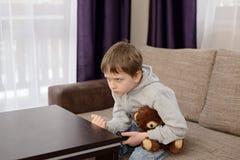 Niño enfadado que se sienta en el sofá y la TV de observación Fotografía de archivo libre de regalías
