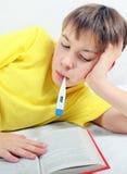 Niño enfermo con el termómetro Foto de archivo