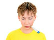 Niño enfermo con el termómetro Imagenes de archivo
