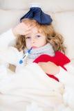 Niño enfermo con fiebre y la botella de agua caliente fotografía de archivo libre de regalías