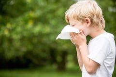 Niño enfermo con un estornudo frío imágenes de archivo libres de regalías