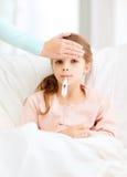 Niño enfermo de la muchacha con el termómetro y la madre que cuida Imagen de archivo