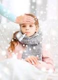 Niño enfermo de la muchacha con el termómetro y la madre que cuida Imagenes de archivo