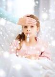 Niño enfermo de la muchacha con el termómetro y la madre que cuida Foto de archivo