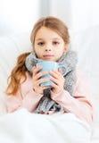 Niño enfermo de la muchacha con la taza de té caliente Fotos de archivo libres de regalías