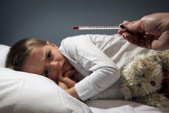 Niño enfermo en cama con temperatura alta Imagen de archivo libre de regalías