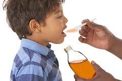 Niño enfermo que toma el jarabe contra tos o gripe Fotos de archivo