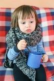 Niño enfermo triste en bufanda de lana caliente con la taza de té Foto de archivo