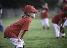 Niño enfocado listo para jugar la bola Imagenes de archivo