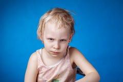Niño enojado en un fondo azul Fotos de archivo libres de regalías