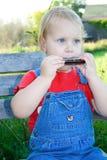 Niño eyed azul que toca la armónica. fotos de archivo libres de regalías