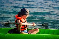 Niño feliz activo, escolar adolescente, divirtiéndose disfrutando de experiencia aventurera kayaking en el río en un día soleado Fotografía de archivo libre de regalías