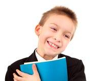 Niño feliz con el libro de ejercicio Imagen de archivo libre de regalías