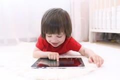 Niño feliz con el ordenador de la tablilla Foto de archivo