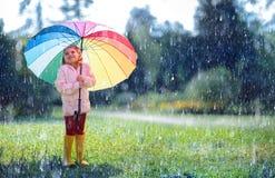 Niño feliz con el paraguas del arco iris fotografía de archivo