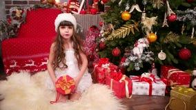 Niño feliz con el regalo del ` s del Año Nuevo, primer de la niña en el traje virginal de la nieve, día de fiesta de la feliz Nav metrajes