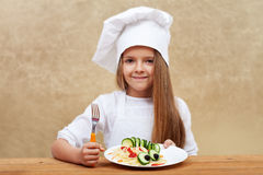 Niño feliz con el sombrero del cocinero y el plato adornado de las pastas Foto de archivo