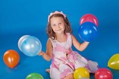 Niño feliz con impulsos coloridos del aire sobre azul Foto de archivo libre de regalías