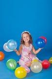 Niño feliz con impulsos coloridos del aire sobre azul Fotografía de archivo